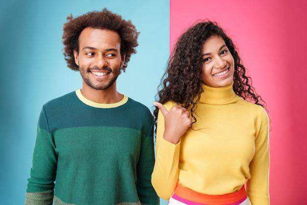 Cheerful young womna debout et pointant sur son petit ami sur fond coloré