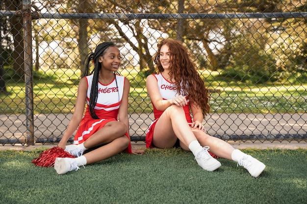Cheerleaders à plein coup assis ensemble