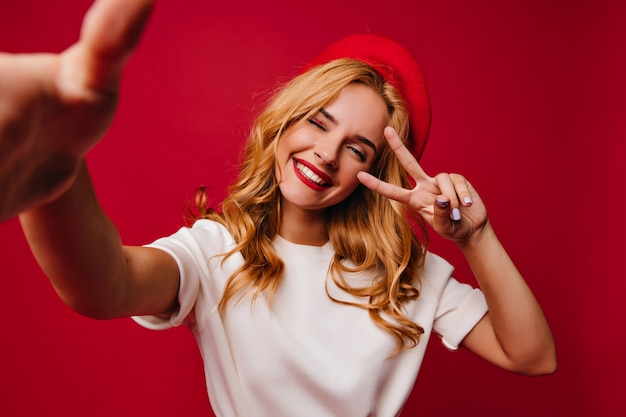 Cheerul belle femme faisant selfie sur mur rouge. tir intérieur de l'élégante fille française insouciante souriant