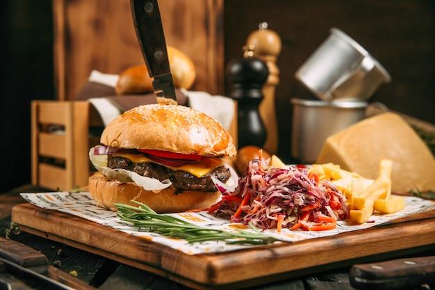 Cheeseburger appétissant avec un couteau et chou salade lente sur la planche de bois sur le fond en bois, vue latérale, horizontal