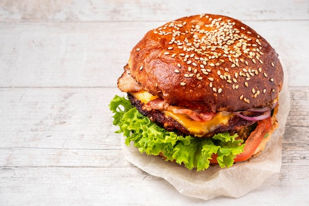 Cheeseburger au bacon sur une table en bois blanche