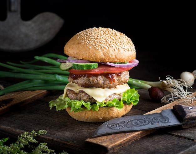 Cheeseburger aux légumes sur une vieille planche de bois brune