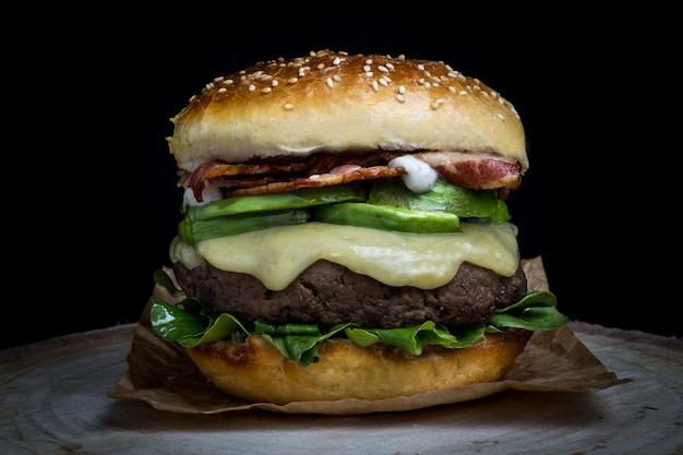 Cheeseburger avec bacon, avocat, laitue et mayonnaise