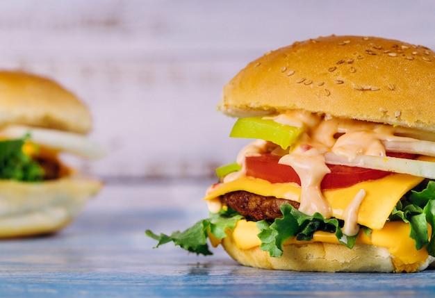 Cheeseburger avec du fromage fondu sur une table blanche.