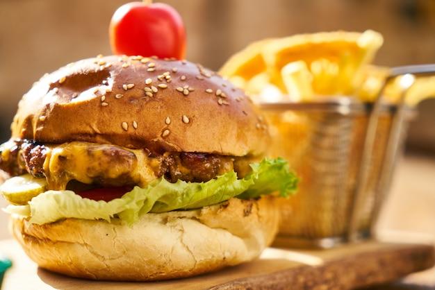 Cheeseburger avec des frites sur la table en bois