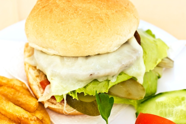Cheeseburger avec des frites, des tranches de concombre et des tomates