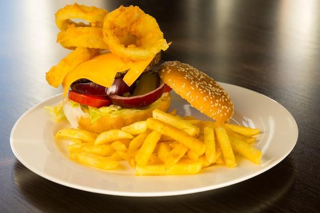 Cheeseburger gastronomique empilé avec des garnitures avec des frites sur la plaque