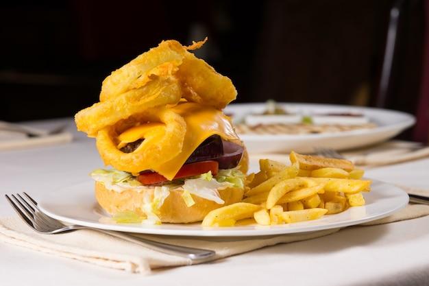 Cheeseburger gastronomique et frites sur la plaque à la place sur la table du restaurant