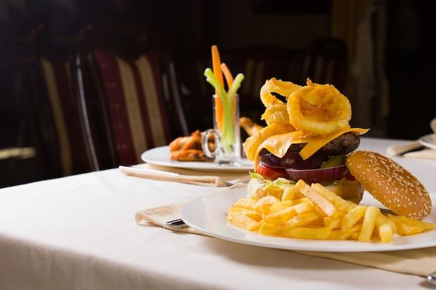 Cheeseburger gastronomique et frites sur table au restaurant