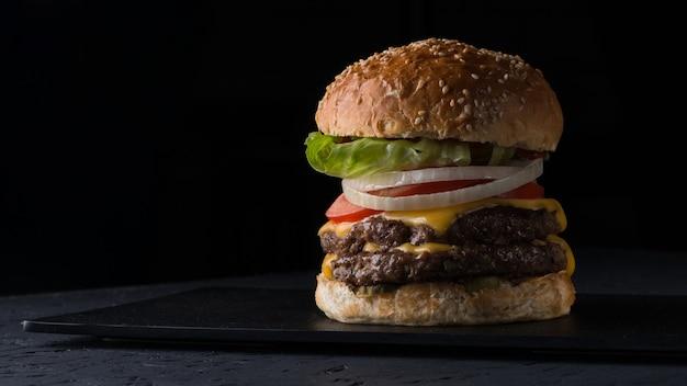 Cheeseburger juteux sur une assiette plate sur fond noir, gros plan