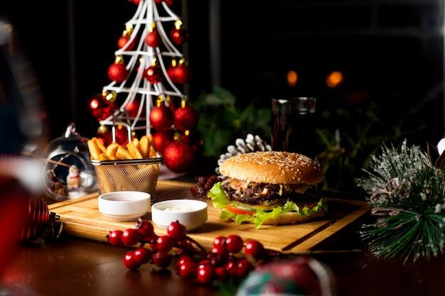 Cheeseburger juteux avec des frites sur une planche de bois