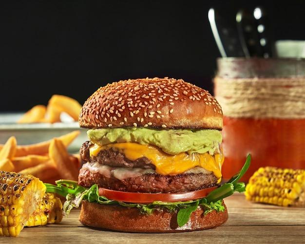 Cheeseburger mexicain avec deux galettes de tomate guacamole et verts