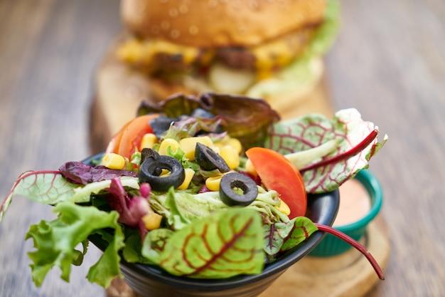 Cheeseburger avec salade sur la table en bois