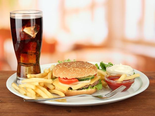 Cheeseburger savoureux avec pommes de terre frites et boisson froide, sur brillant