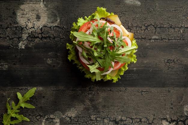 Cheeseburger sur une vieille surface en bois de couleur foncée hamburger avec viande et tomate
