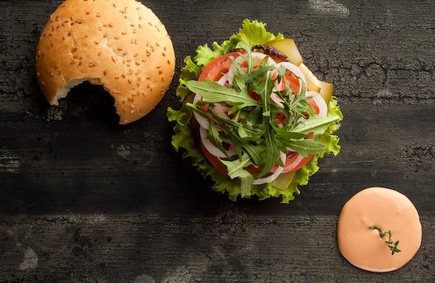 Cheeseburger sur une vieille surface en bois de hamburger de couleur foncée avec sauce et ketchup