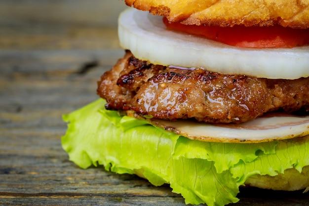 Cheeseburgers sur des galettes de boeuf et des ingrédients de salade fraîche servis avec sur une table en bois rustique