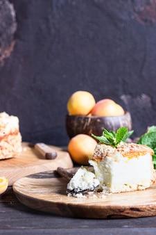 Cheesecake avec abricot et crumble, abricots frais et menthe.