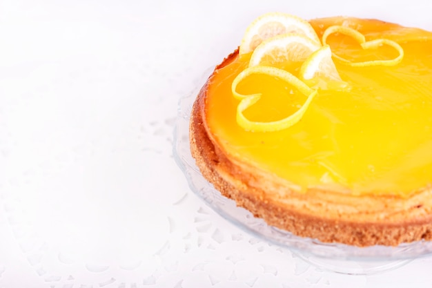 Cheesecake au citron sur fond blanc orné de zeste de citron se bouchent
