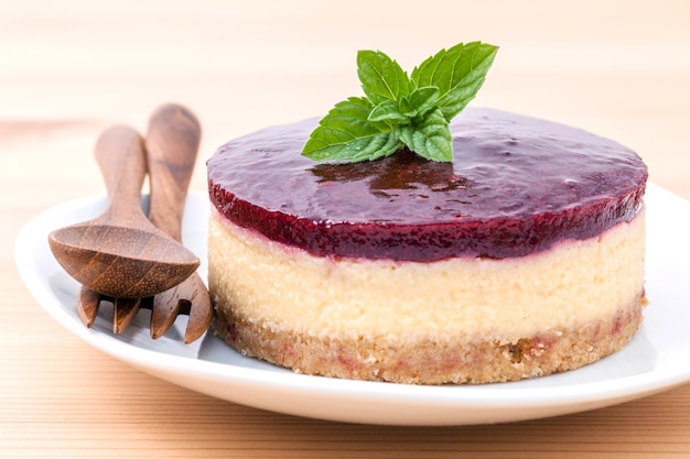 Cheesecake aux bleuets avec des feuilles de menthe fraîche sur fond de bois.