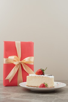 Cheesecake aux fraises et un cadeau sur table en marbre.