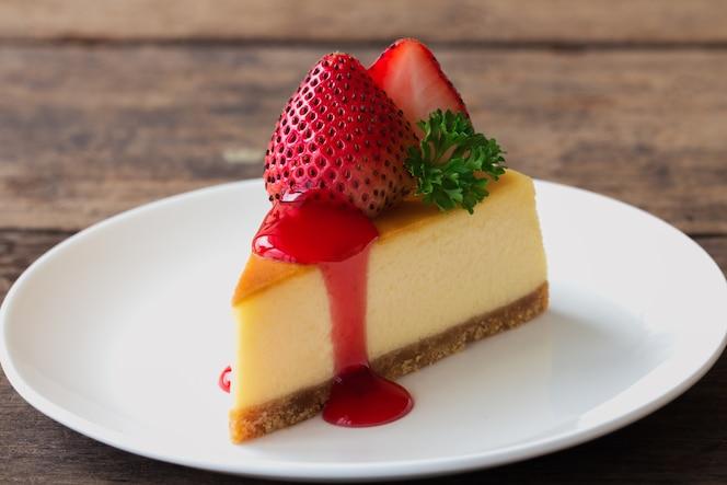 Cheesecake aux fraises maison orné de fraises fraîches sur assiette blanche.