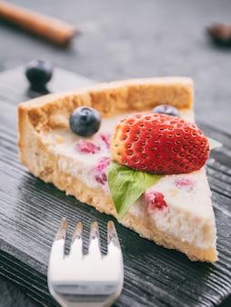 Cheesecake aux fraises et myrtilles sur support en bois ou surface, gros plan