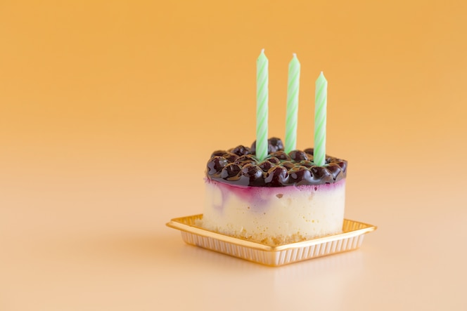 Cheesecake aux myrtilles avec des bougies sur un fond jaune