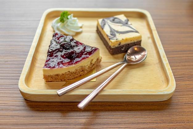 Cheesecake aux myrtilles servi sur une assiette en bois.