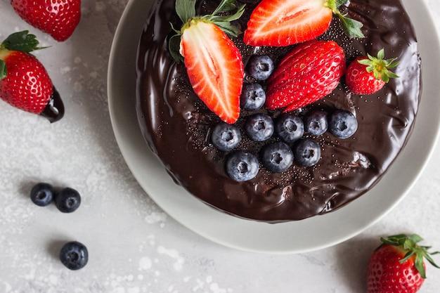 Cheesecake aux raisins secs décoré de glaçage au chocolat et de fraises et myrtilles.