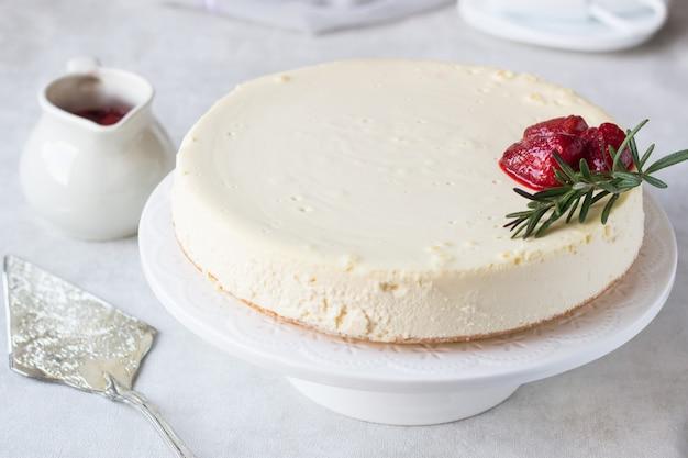 Cheesecake classique de new york avec sauce à la fraise et romarin