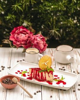 Cheesecake coulé au sirop de fraises avec une tranche d'orange