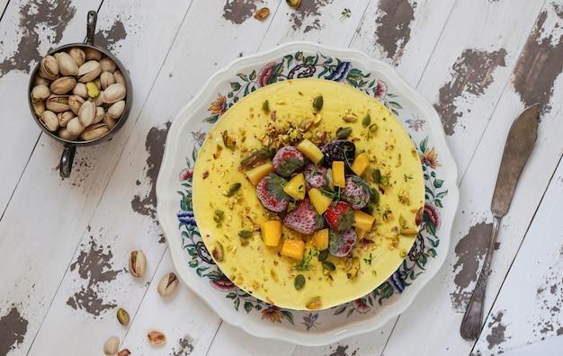 Cheesecake cru végétalien avec myrtille, cerise, thé au matcha, orange, crème de noix de cajou, beurre de coco et lait de coco, et base en amandes, dattes et abricots secs, flocons d'avoine, baies lyophilisées