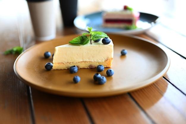 Cheesecake dessert sur une assiette avec des bleuets dans un restaurant avec une feuille de menthe