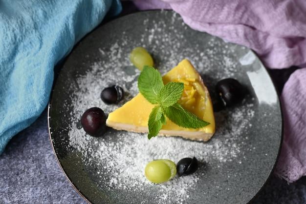 Cheesecake dessert sur une assiette avec du raisin dans un restaurant avec une feuille de menthe