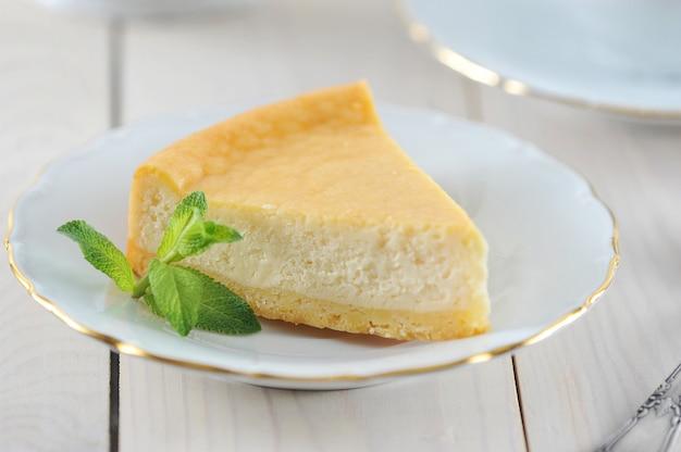 Cheesecake et une feuille de menthe sur la soucoupe avec un bord doré