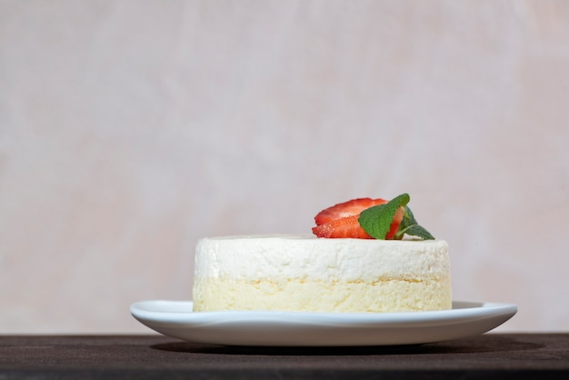 Cheesecake avec fraises fraîches et menthe sur plat blanc. dessert au fromage délicat.