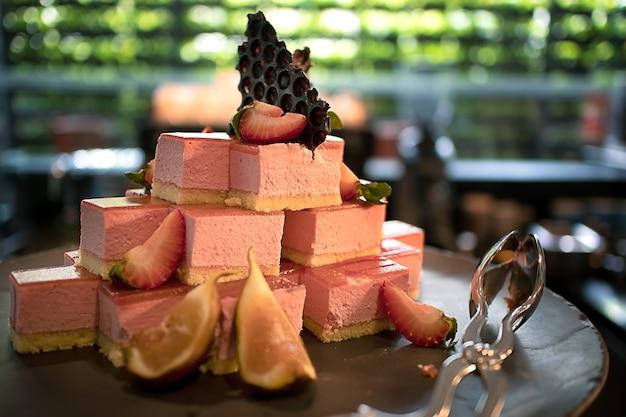 Cheesecake à la framboise rose en petits morceaux dans un comptoir de pâtisserie et de boulangerie