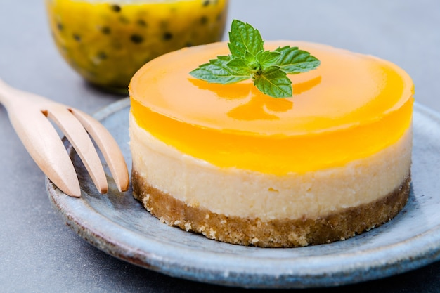 Cheesecake de fruits de la passion avec des feuilles de menthe fraîche sur fond sombre.