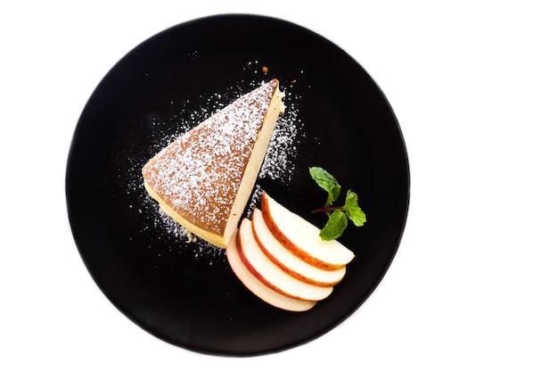 Cheesecake japonais sur plaque noire. servi avec garniture de glaçage et tranches de pommes.