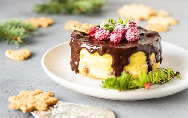 Cheesecake de new york avec ganache au chocolat, framboises et biscuits avec des branches de sapin.