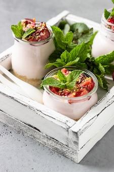 Cheesecake non cuit au four avec des cerises dans des bocaux en verre, des cerises fraîches et de la menthe. dessert sain.