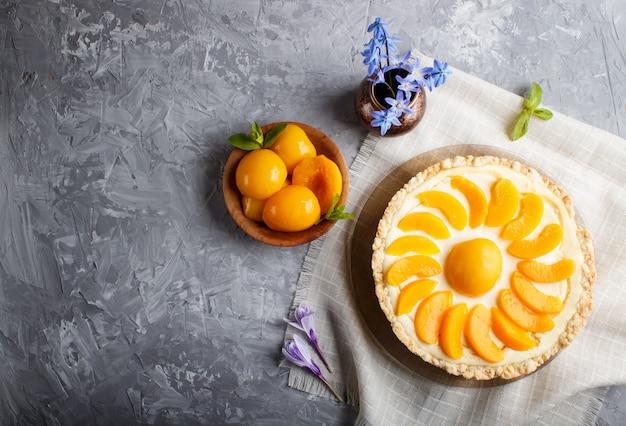 Cheesecake à la pêche et vase en céramique à fleurs bleues sur un béton gris. vue de dessus.