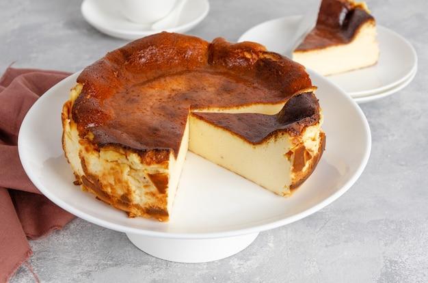 Cheesecake de saint-sébastien sur le dessus sur une plaque blanche sur un fond de béton gris. dessert traditionnel espagnol. copiez l'espace.