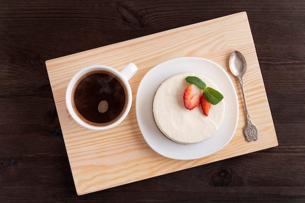 Cheesecake et tasse de café sur un plateau en bois. bon petit déjeuner. vue de dessus