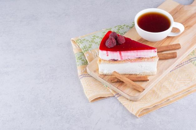 Cheesecake et tasse de thé noir sur planche de bois.