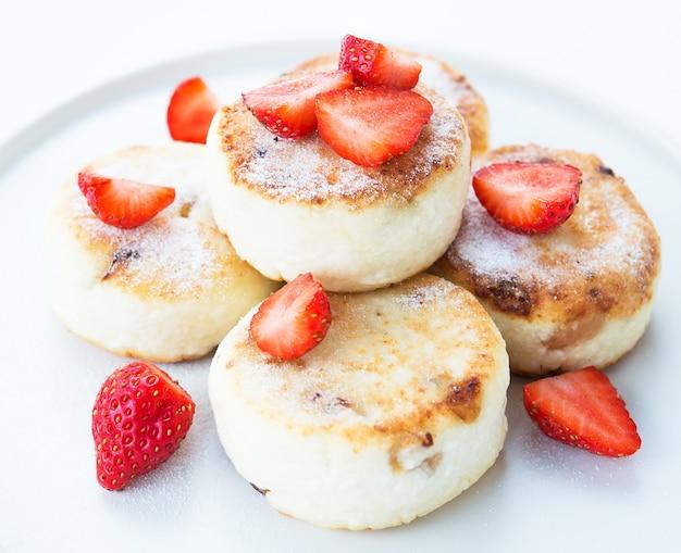 Cheesecakes au fromage cottage avec des fraises et du sucre en poudre, close up