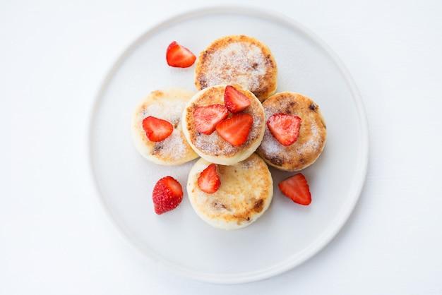 Cheesecakes au fromage cottage avec des fraises et du sucre en poudre, vue du dessus