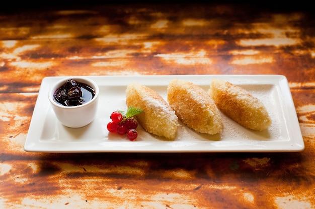 Cheesecakes à kiev avec de la confiture et des baies de cassis sur une plaque rectangulaire blanche.