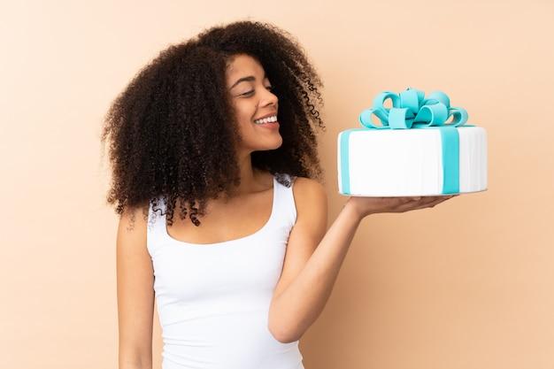 Chef afro pâtissier tenant un gros gâteau sur le mur beige avec une expression heureuse